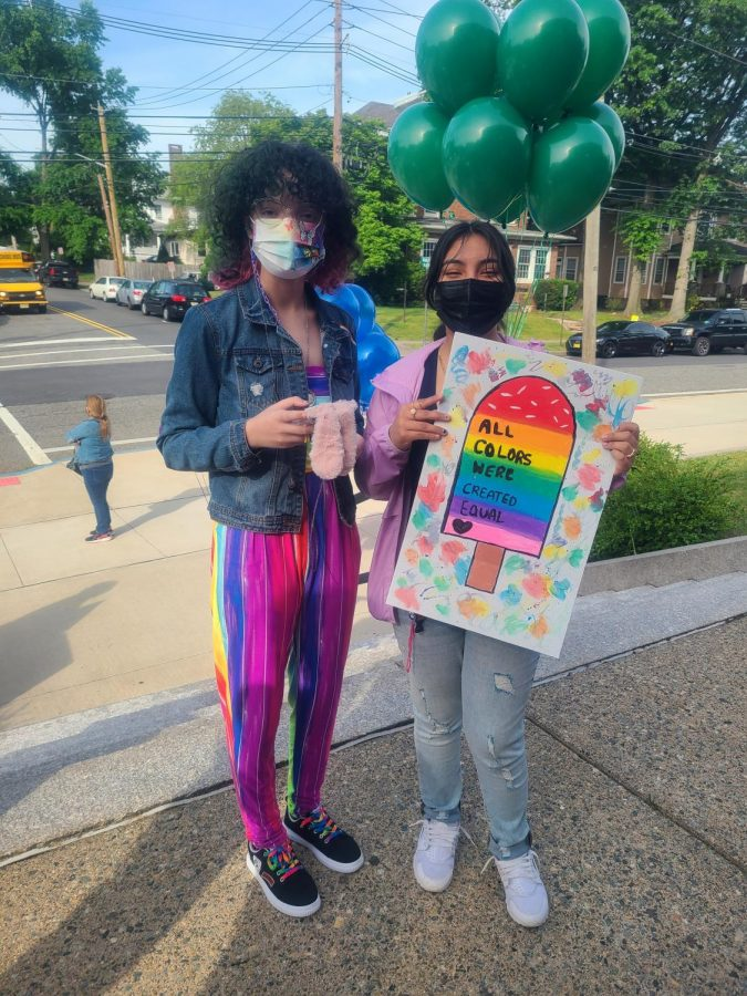 """One student holds a sign that says """"All colors were created equal."""